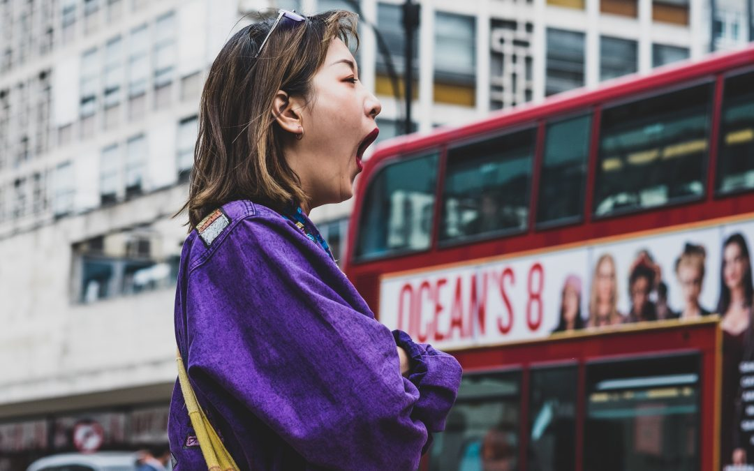Woman standing on a street and yawning
