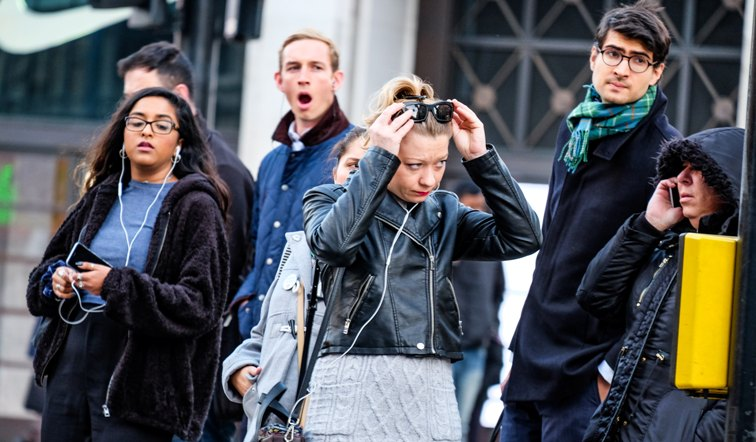 A group of people.  One is talking on a mobile phone, one woman has earbud headsets and is holding her phone another has headsets leading to a bag which is close to her body.  There are men in the background not on phones.