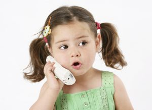 An image of a young girl using a cordless phone. The girl appears to be around 3 years old.